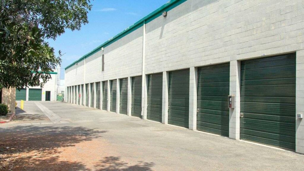 A row of large outdoor storage units with green doors in a clean area