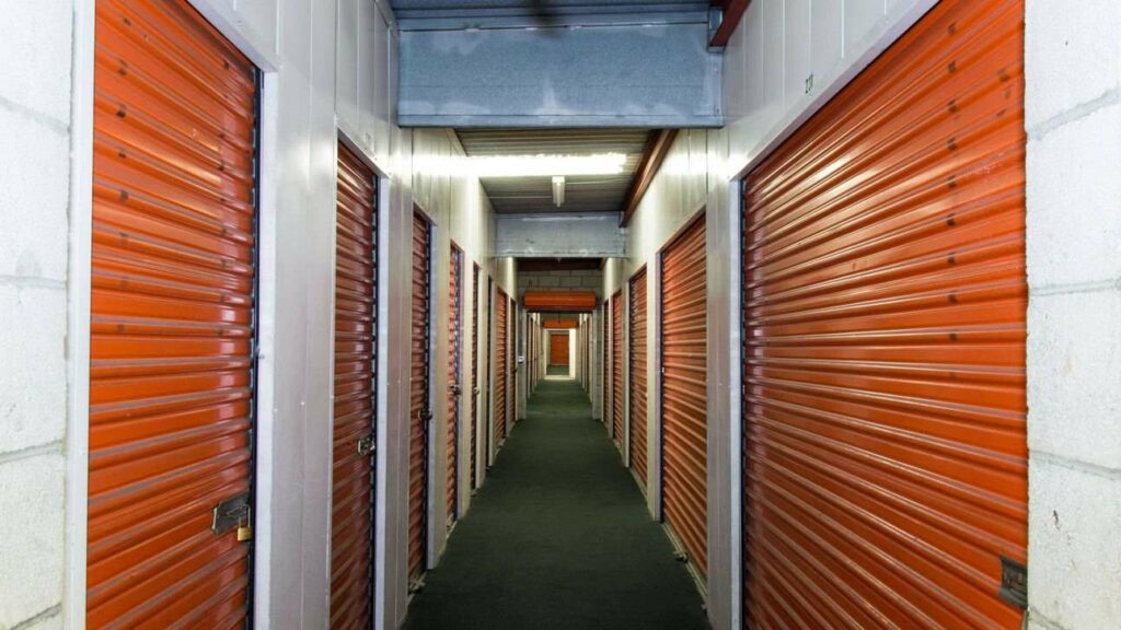 A long row of indoor storage units with orange doors in a well lit hallway