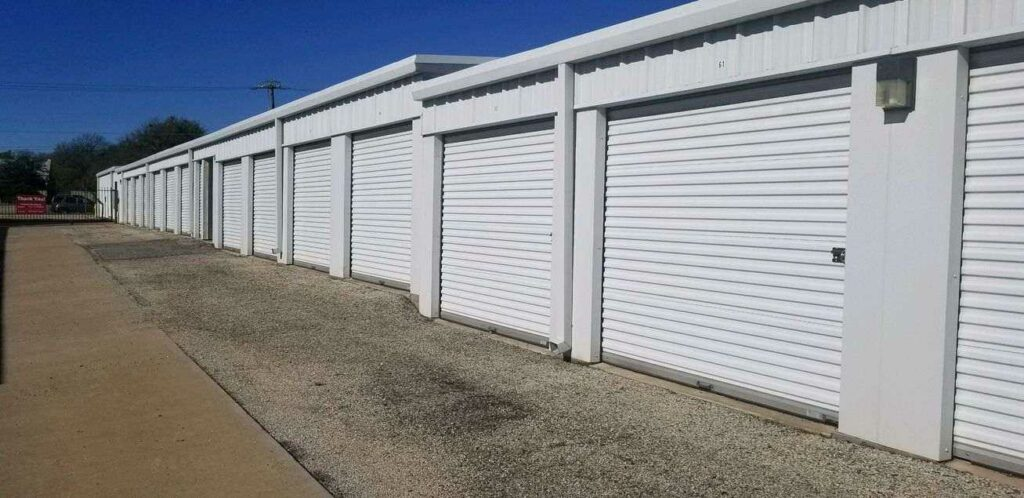 A row of large outdoor storage units with white doors in a clean area