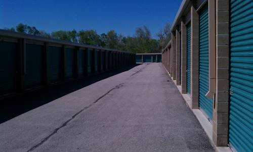 A row of large outdoor storage units with blue doors in a clean area