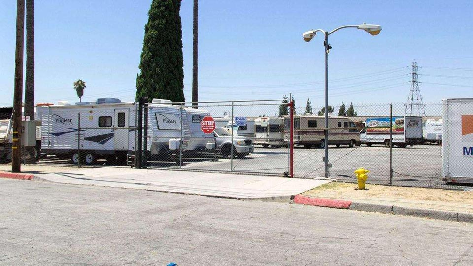 Street side view of gated entrance to outdoor parking with RVs, trailers, and trucks