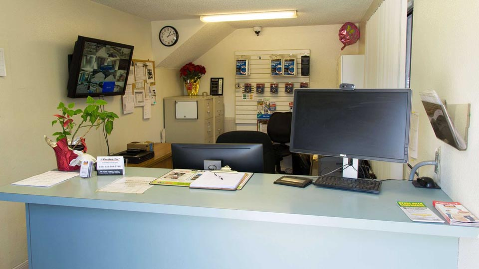 Front desk inside storage facility with supplies available and security surveillance