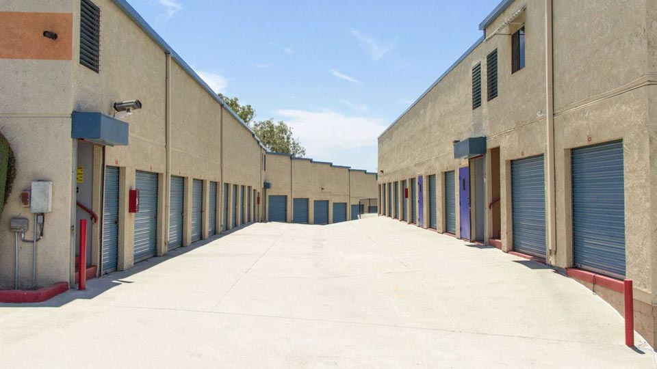 Long row of large outdoor storage units with blue doors