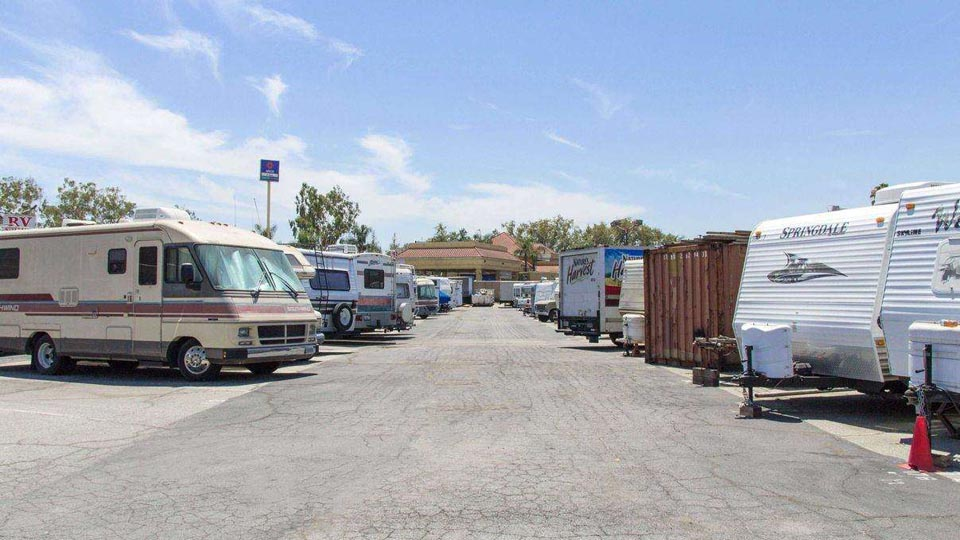 A large parking lot area with RVs, trailers, and trucks parked next to each other