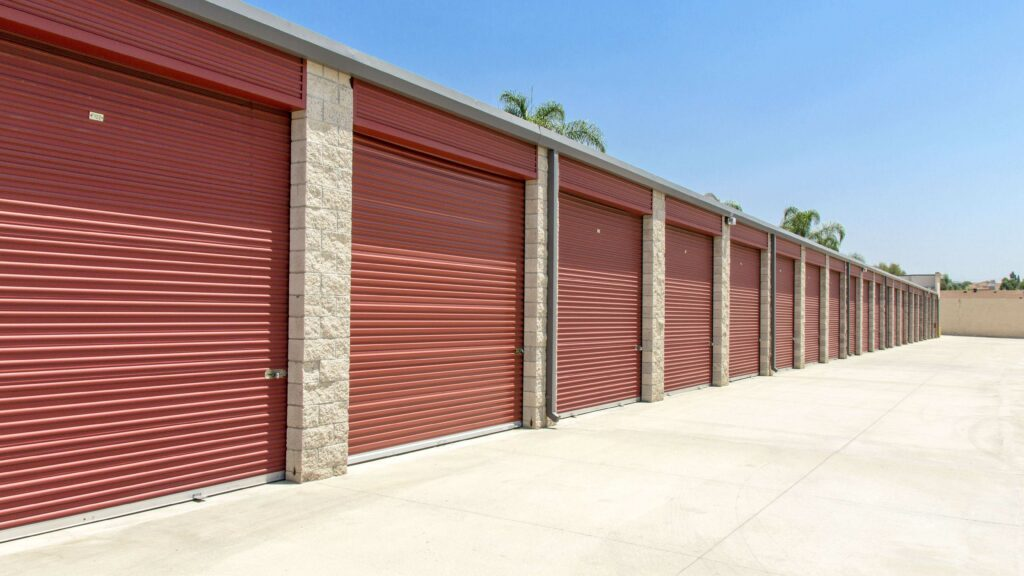 Row of large outdoor storage units with red doors