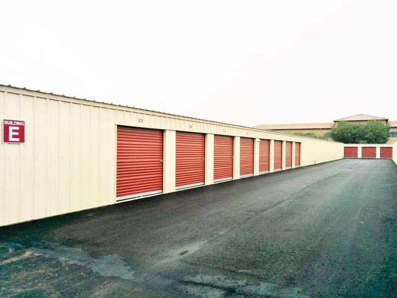 A row of outdoor storage units with red doors