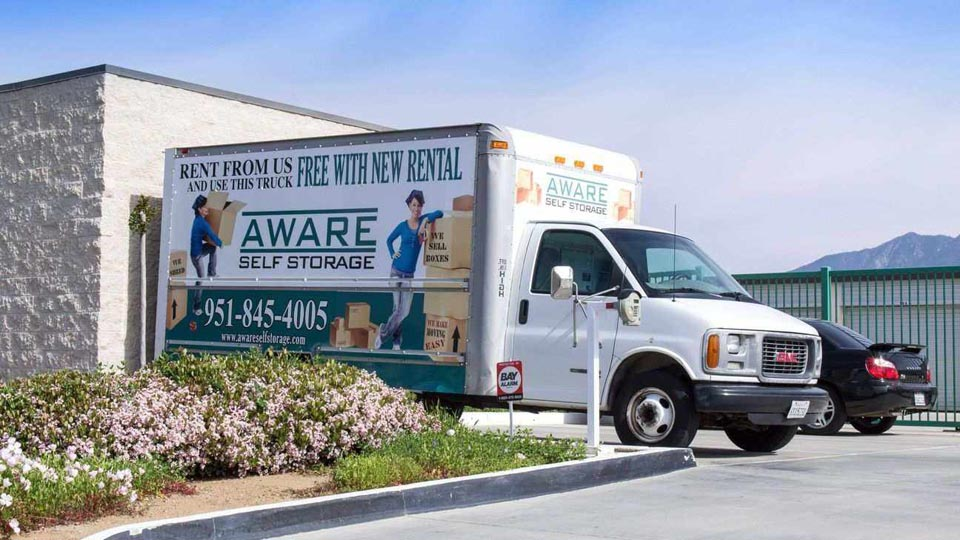 An Aware Self Storage moving truck parked in front of facility