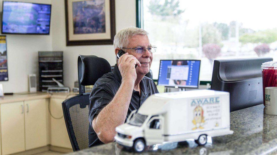 A man on the phone behind the front desk at facility office