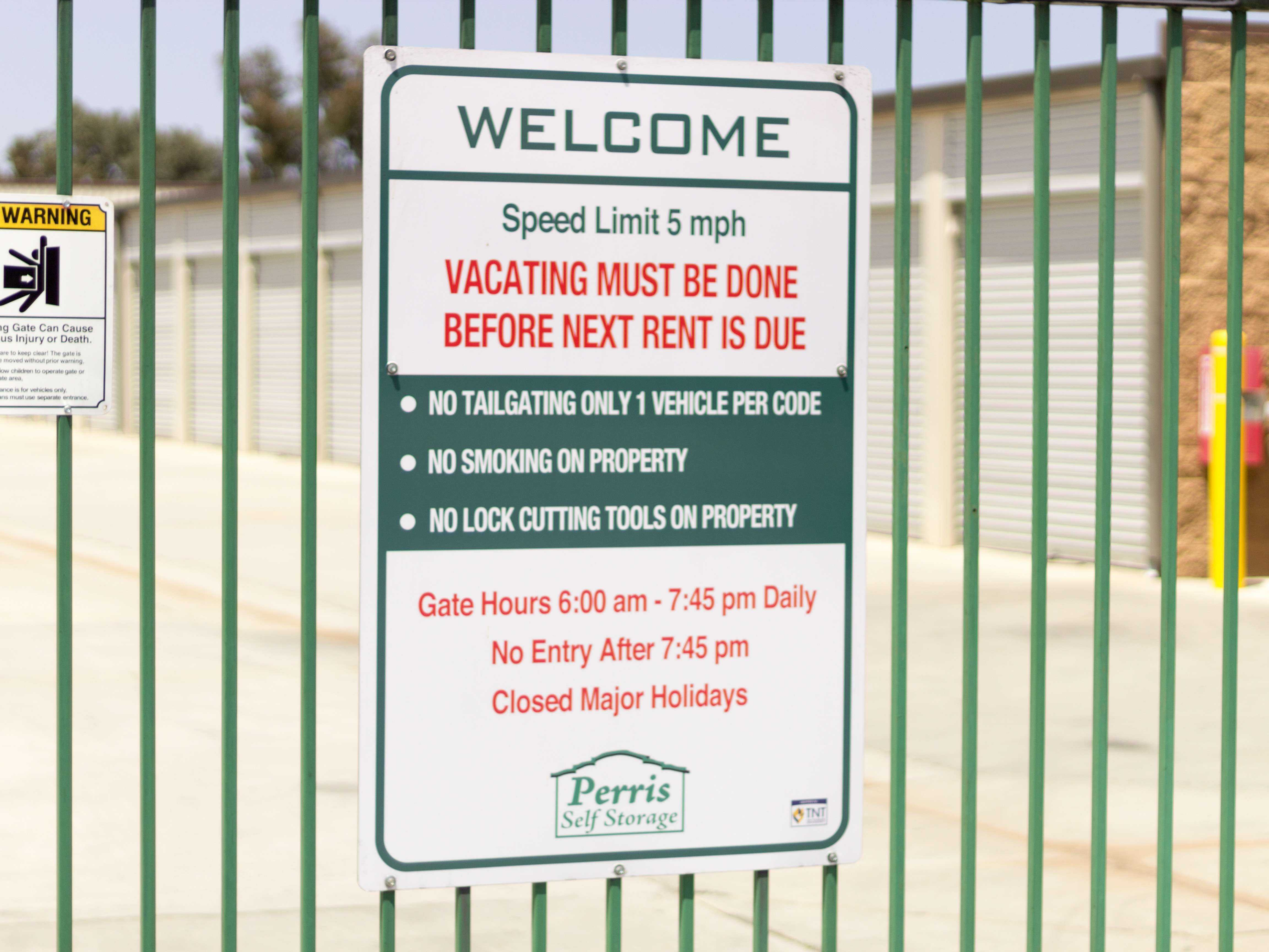 A welcome sign posted on gated entrance to outdoor storage units with hours of 6:00am to 7:45am daily