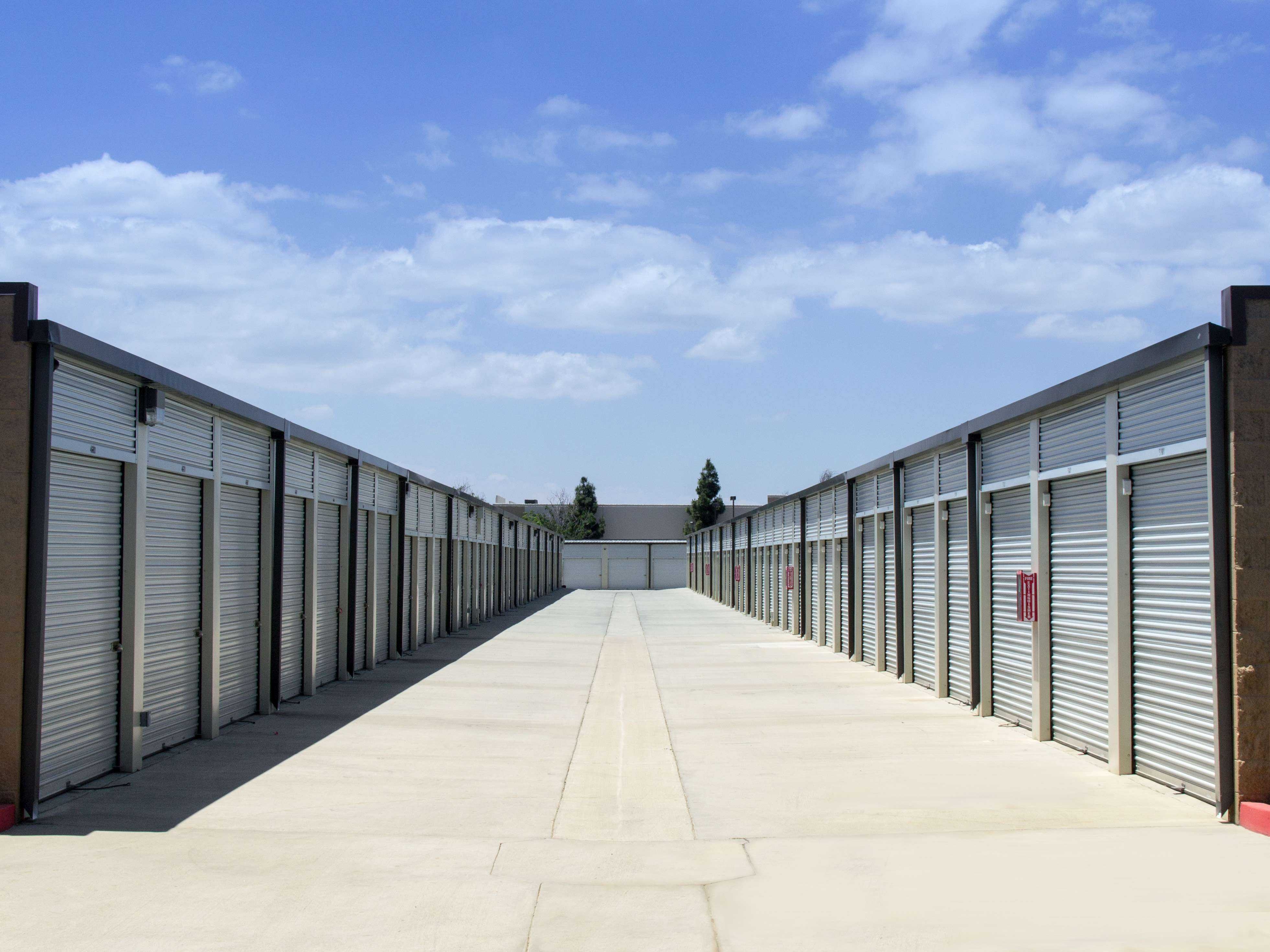 A long row of large outdoor storage units with white doors in a clean, open area