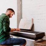 man sitting at at keyboard playing sheet music