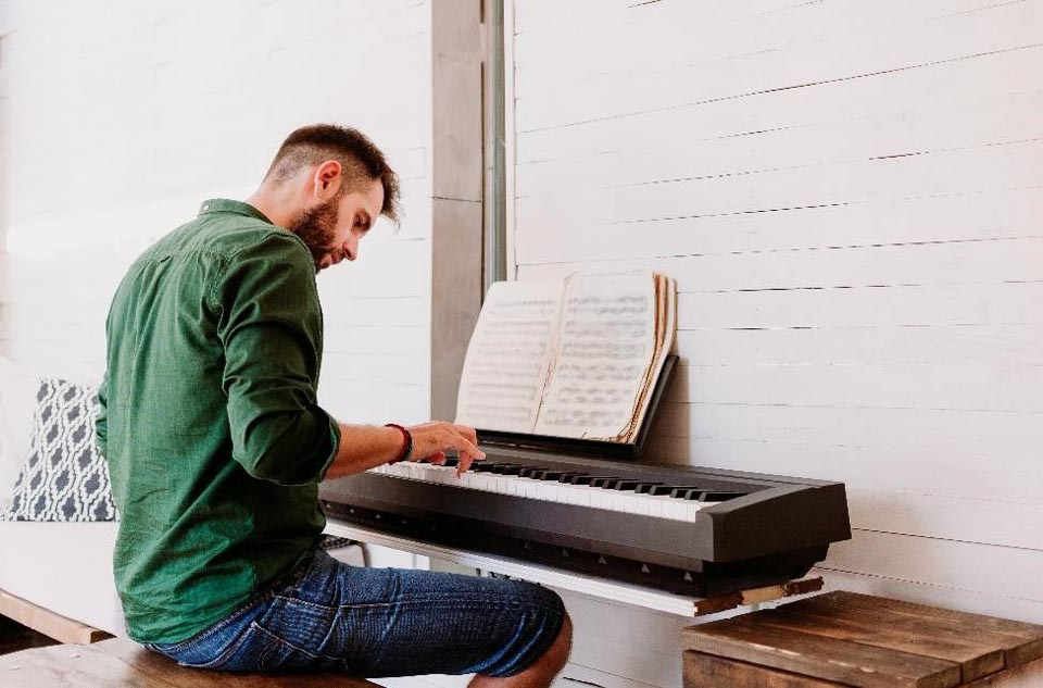 man sitting at at keyboard playing sheet music