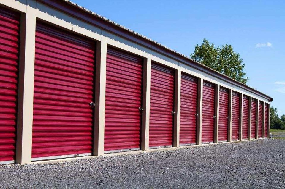 A row of outdoor storage units with red doors in a clean area