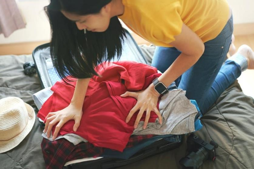 A woman trying to pack an overflowing suitcase of clothes