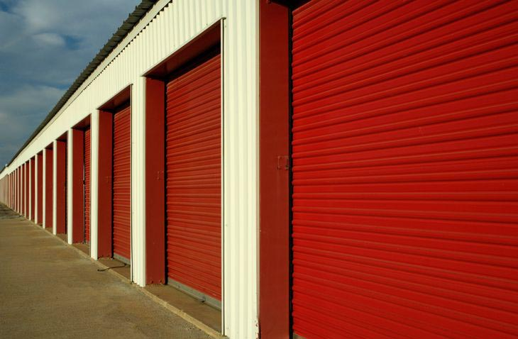 Row of outdoor storage units with large, red doors in a clean area